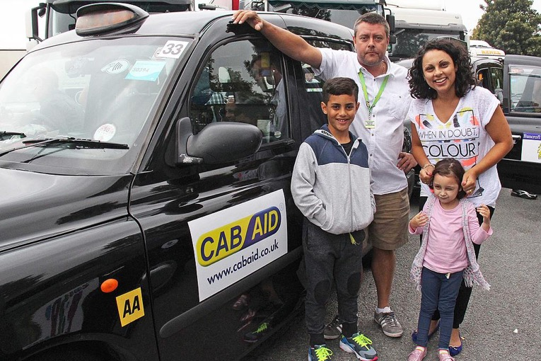 Two children and their mother stand aside a black cab smiling happily with the driver.